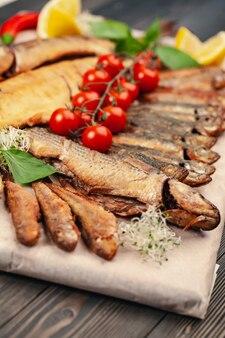 Plat de poisson grillé au four entier grillé sur une plaque avec des légumes et du citron