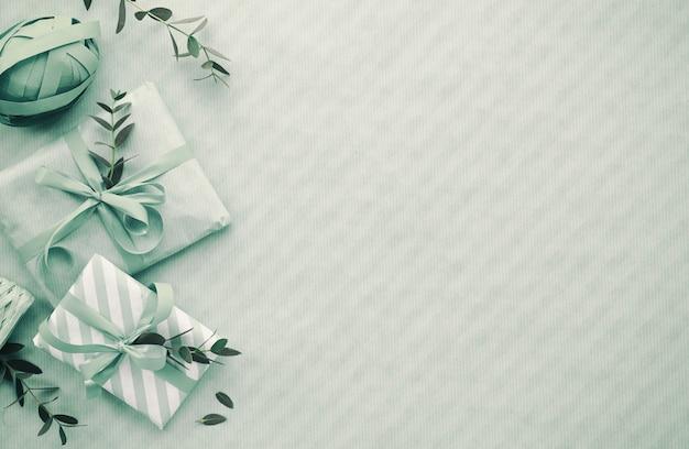 Plat posé en bleu clair avec boîtes-cadeaux emballées décorées de brindilles d'eucalyptus, espace de copie