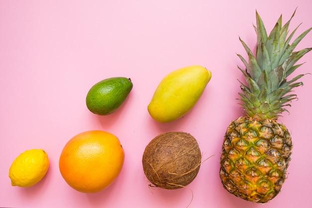 Plat posé avec des fruits tropicaux sur fond rose: noix de coco, ananas, mangue, pamplemousse, citron, avocat