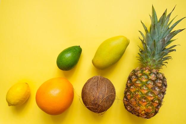 Plat posé avec des fruits tropicaux sur jaune: noix de coco, ananas, mangue, pamplemousse, citron, avocat