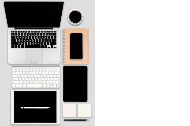 Plat pose de table de bureau avec ordinateur portable, tablette numérique, téléphone mobile et accessoires.