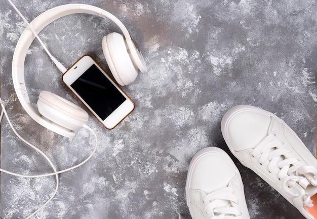 Plat poser de baskets blanches sur pierre fond avec téléphone et des écouteurs.