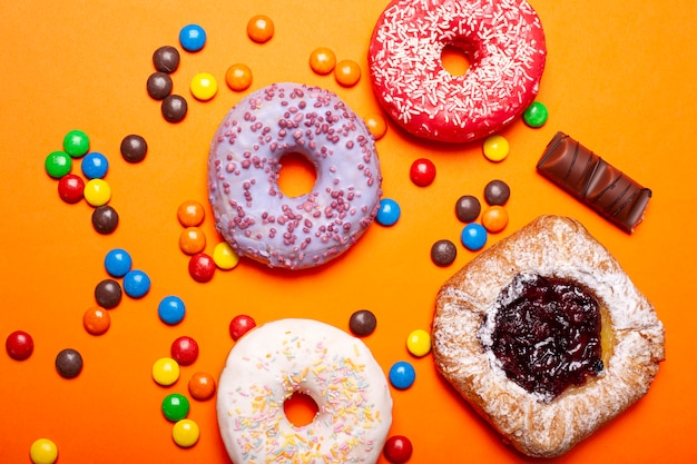 Plat poser des beignets assortis colorés glacés doux petits bonbons et chignon avec jem sur une vue de dessus d'arrière-plan de couleur orange vif.