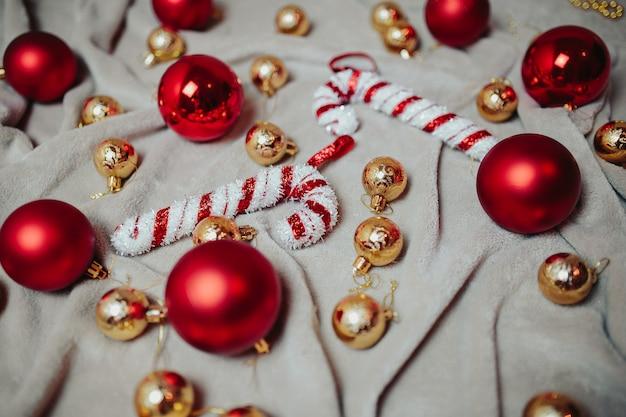 Plat poser avec des boules de noël rouges, boules de noël dorées et des cannes de bonbon de noël sur le plaid.