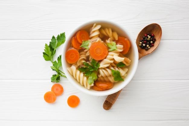 Plat poser le brocoli fusilli et les carottes dans un bol avec une cuillère en bois