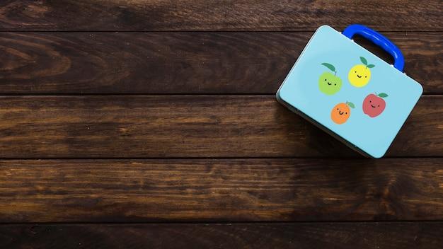 Plat poser de cas d'enfant bleu sur la surface en bois