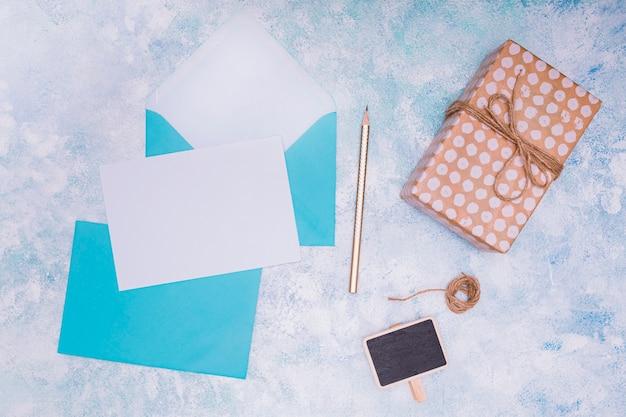 Plat poser avec enveloppe bleue et invitation d'anniversaire mock up