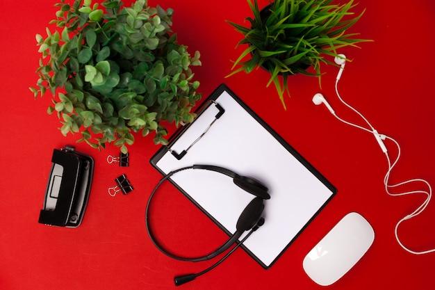 Plat poser des fournitures d'espace de travail sur fond rouge
