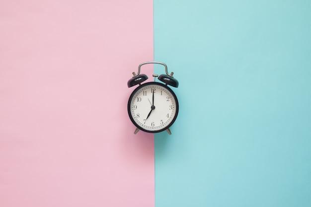 Plat poser horloge sur fond rose et bleu