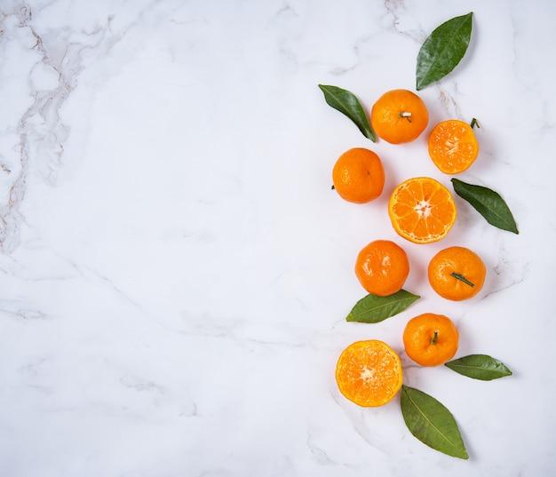 Plat poser des mandarines douces et des feuilles vertes
