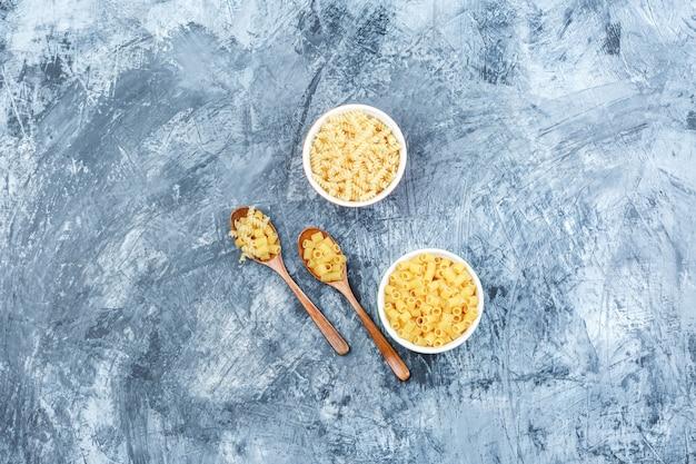 Plat poser des pâtes crues dans des bols et des cuillères en bois sur fond de plâtre sale. horizontal