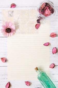 Plat poser la photographie de stock pétales de fleurs violettes lettre enveloppe papier transparent bouteille en verre vert