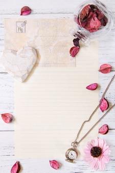 Plat poser photographie de stock pétales de fleurs violettes lettre enveloppe papier verre transparent bouteille poche horloge coeur artisanat