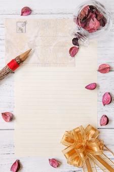 Plat poser la photographie de stock pourpre fleur pétales lettre enveloppe papier verre bouteille bois crayon ruban doré