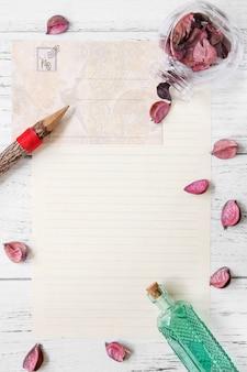 Plat poser la photographie de stock pourpre fleur pétales lettre enveloppe papier verre bouteille bois crayon