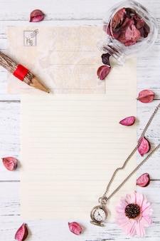 Plat poser la photographie de stock violet fleur pétales lettre enveloppe papier verre transparent bouteille poche horloge bois crayon