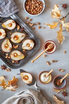 Plat poser avec un plateau de poires cuites au four avec des noix caramélisées sur fond de béton gris