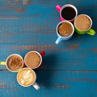 Plat poser quelques tasses avec du café sur fond de fond en bois bleu, copiez l'espace pour le texte.