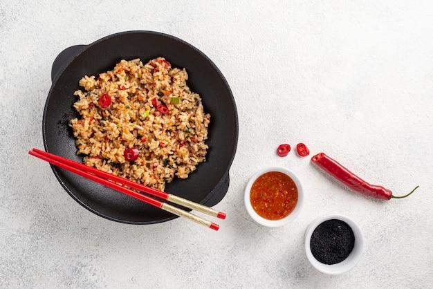 Plat poser riz et légumes sur assiette avec des baguettes