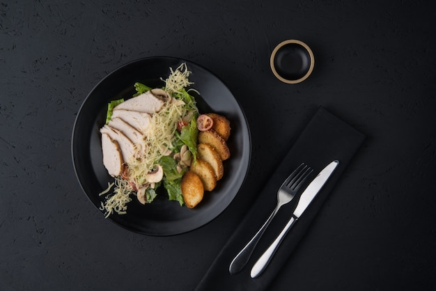 Un plat de poulet sur la surface en bois noir, vue de dessus