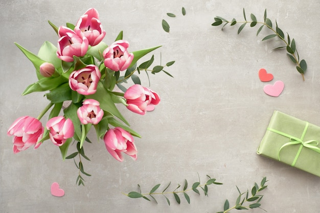Plat de printemps avec bouquet de tulipes roses, feuilles d'eucalyptus et coffrets cadeaux