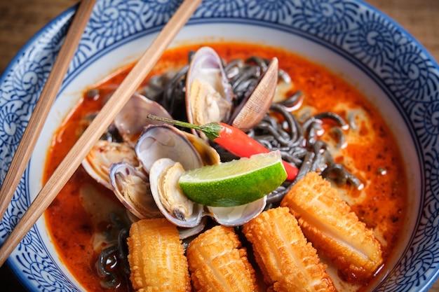 Plat de ramen chaud typique avec bouillon de poisson dans un bol avec nouilles noires, calmars, piment, palourdes.