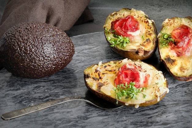 Plat de régime céto: bateaux d'avocat avec bacon croquant, fromage fondu et pousses de cresson sur pierre grise