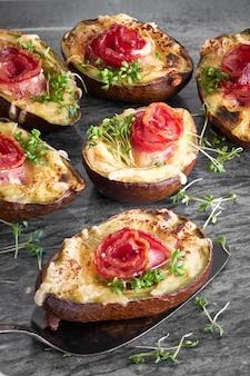 Plat de régime céto: bateaux d'avocat avec bacon croquant, fromage fondu et pousses de cresson sur pierre sombre.