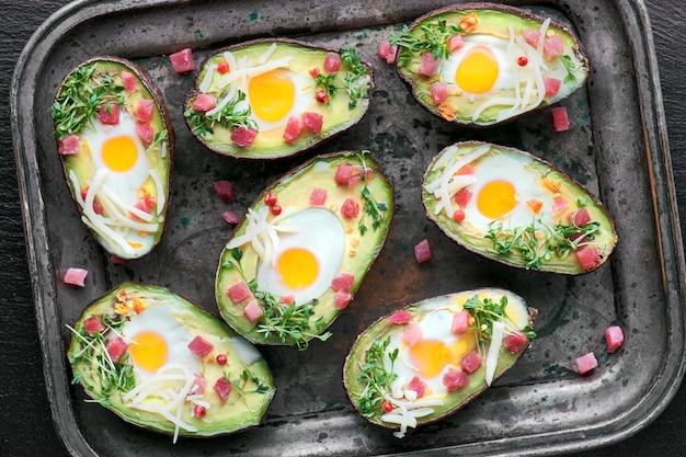 Plat de régime céto: bateaux d'avocat avec des cubes de jambon, des œufs de caille, du fromage et des germes de cresson sur une plaque à pâtisserie