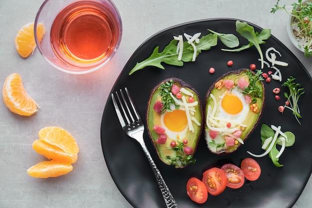 Plat de régime céto: bateaux d'avocat avec des cubes de jambon, des œufs de caille et du fromage, top lay