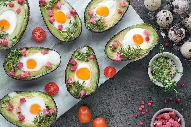 Plat de régime céto: bateaux d'avocat avec des cubes de jambon, des œufs de caille et des tomates cerises sur une planche de service en marbre