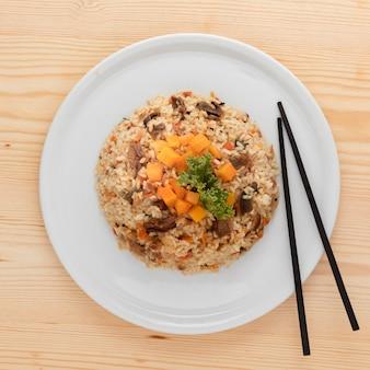 Plat de riz savoureux et baguettes