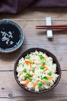 Plat de riz végétarien avec légumes et pois verts sur une surface en bois