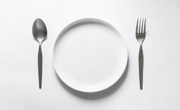 Plat rond en céramique avec fourchette et cuillère en argent, sur tableau blanc
