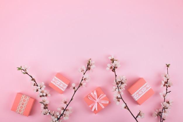 Plat rose poser avec des boîtes-cadeaux de dentelle