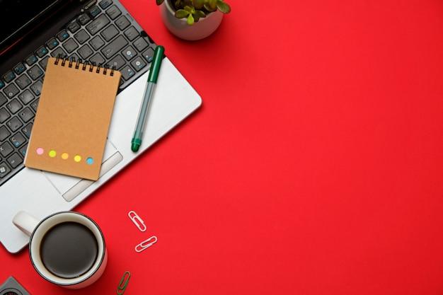 Plat rouge espace de travail moderne plat avec ordinateur portable, lunettes, smartphone, tasse à café.