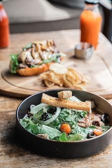 Un plat de salade avec du pain sur une plaque noire avec un fond de hot-dog sur table en bois