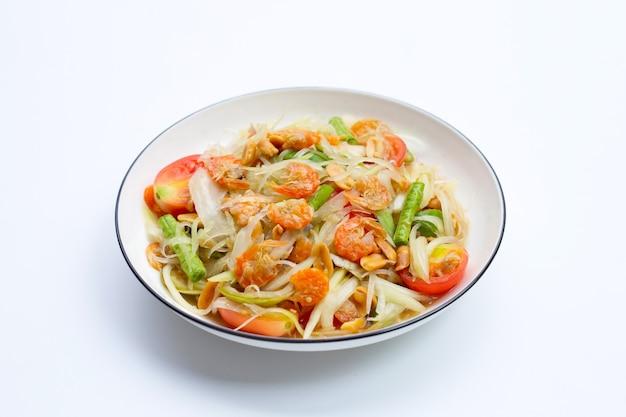 Plat de salade de papaye épicée sur surface blanche