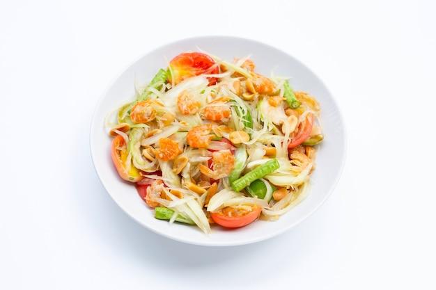 Plat de salade de papaye épicée sur tableau blanc.