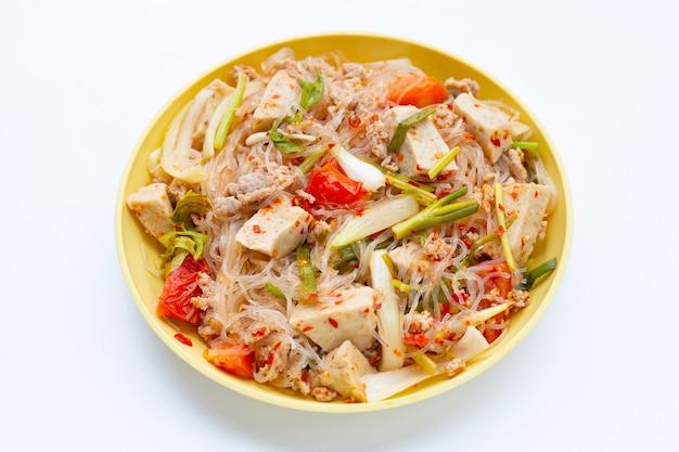 Plat de salade de vermicelles épicée sur fond blanc.