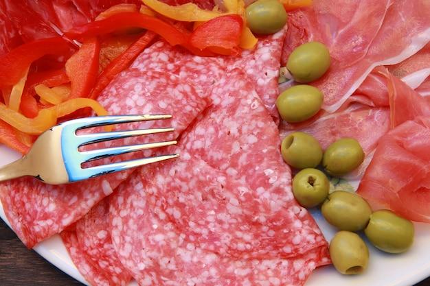 Plat avec salami, jambon et apéritifs