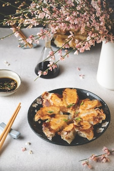 Plat servi de raviolis japonais gyoza frits avec sauce soja sur table lumineuse