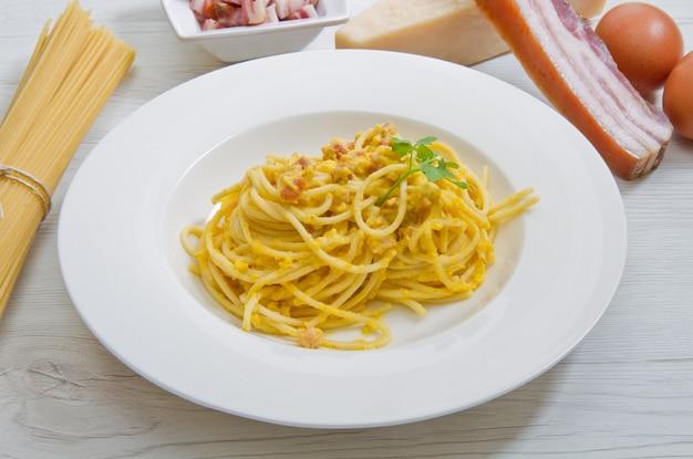 Plat avec des spaghettis de carbonara et des ingrédients