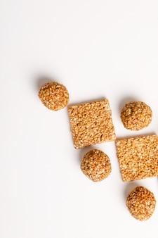 Plat sucré indien, boule de graines de sésame ou appelé en hindi, jusqu'à ce que vous soyez laddu sur fond blanc