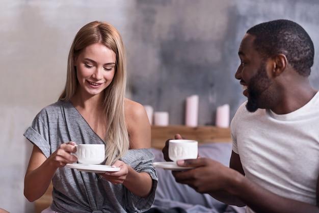 Plat sucré. joyeux jeune couple international mangeant ensemble et souriant assis dans la chambre ensemble.