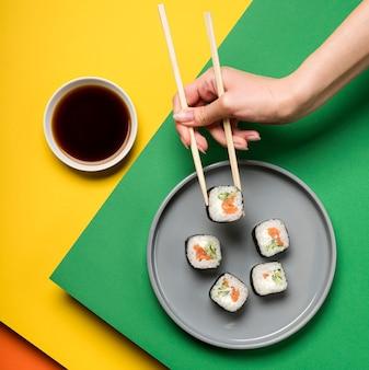 Plat de sushi japonais et main tenant des baguettes