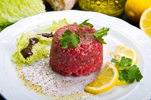 Plat de tartare de viande avec une tranche de citron