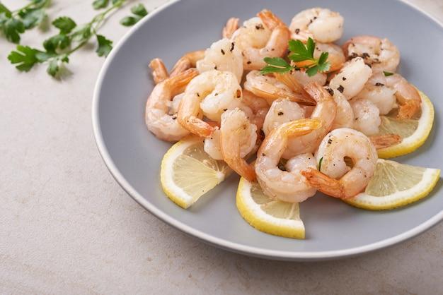 Plat traditionnel de crevettes scampi sur la vue de dessus de la surface en bois. crevettes frites dans une pâte à l'ail avec du citron et du persil. olives, huile, crevettes grillées et salade de légumes frais. la nourriture saine. manger propre