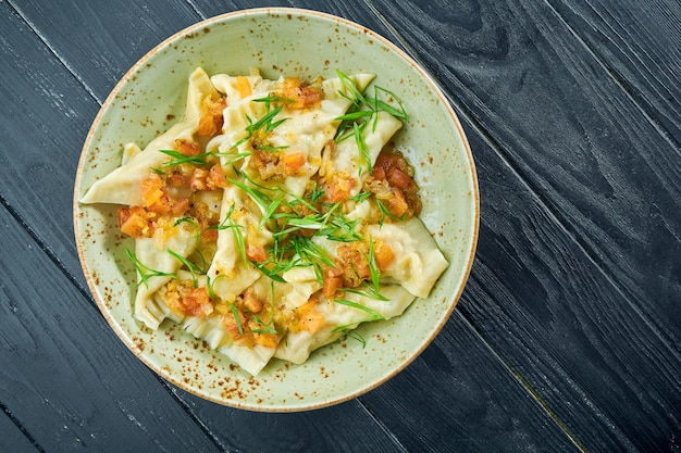 Plat traditionnel de la cuisine israélienne - kreplach de poulet avec salsa de tomates et oignons verts dans une assiette sur une surface en bois noir. nourriture de restaurant. boulettes avec différentes garnitures