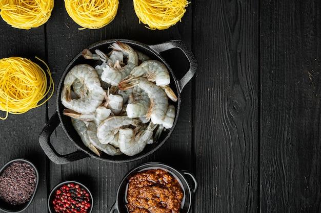 Plat traditionnel italien. pâtes au pesto ricotta parmesan et ingrédients de fruits de mer grillés, sur fond de bois noir, vue de dessus à plat, avec espace de copie pour le texte